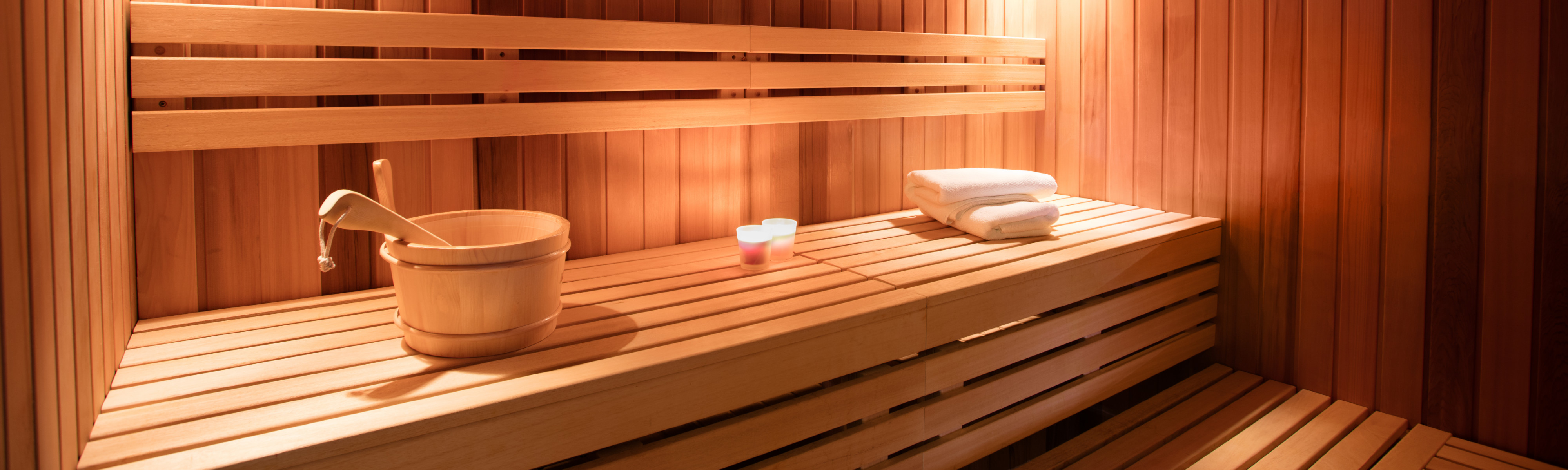 Interior of a beautiful wood sauna with towels and water dipper.