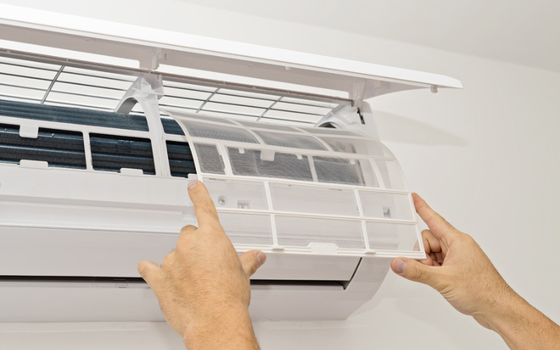 An HVAC technician in Fishersville, VA, servicing a homeowner's ductless air conditioning system.