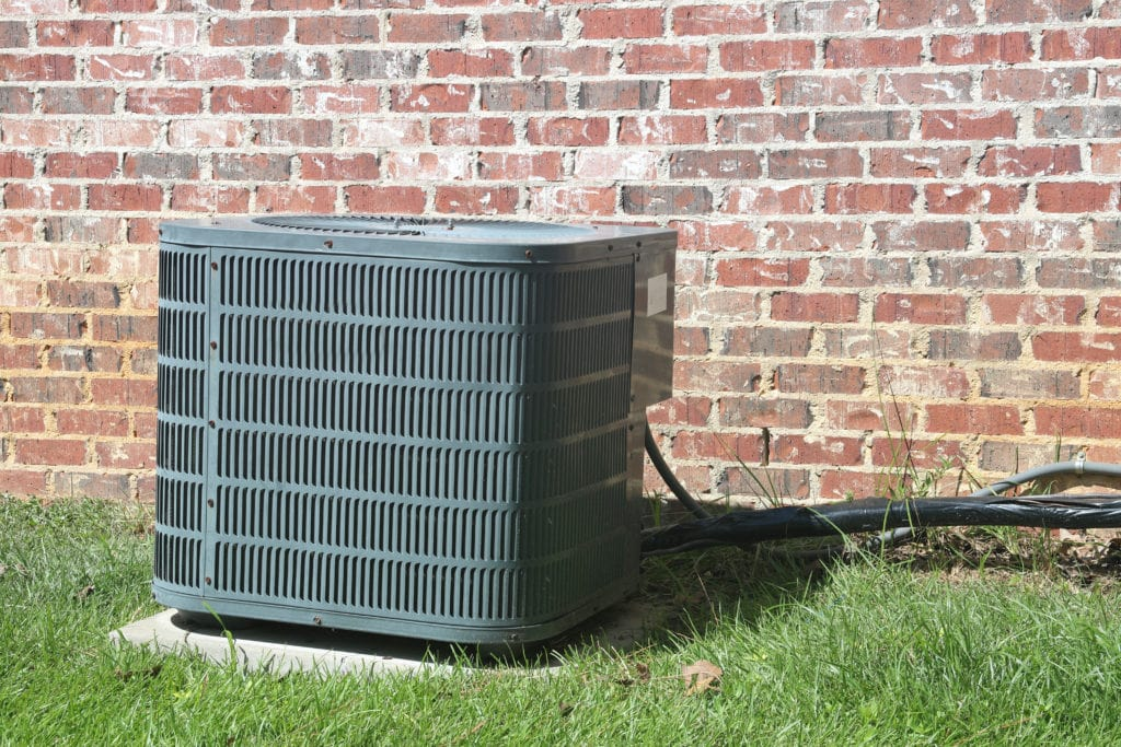 Home Air Conditioner Condenser coil sitting in front of brick wall.