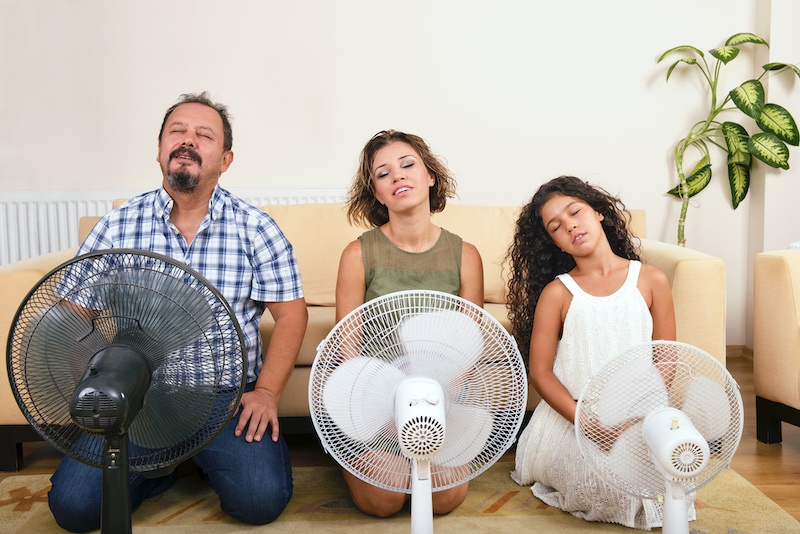 Whole family are sitting on the floor in front of fans because their heat pump is blowing hot air.