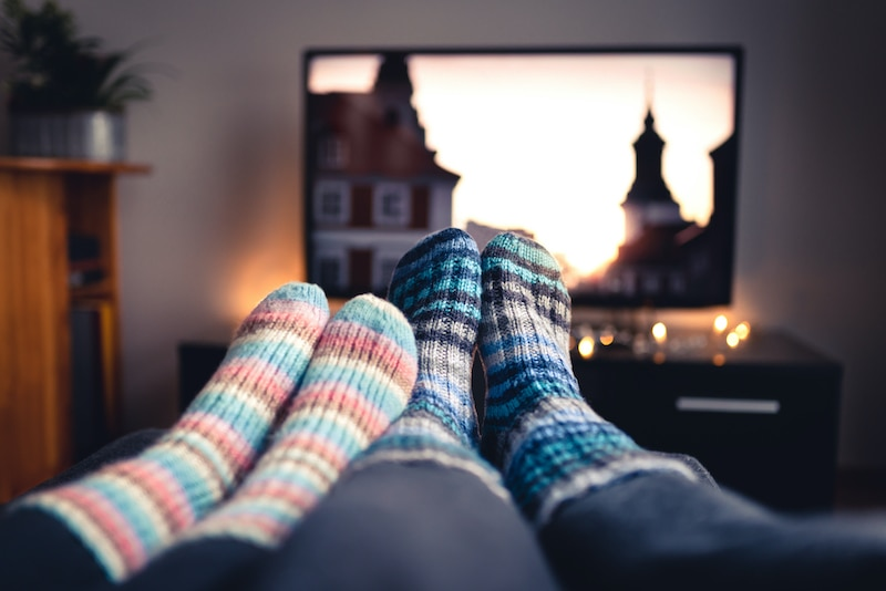 Couple with socks and woolen stockings watching movies or series on tv in winter. Woman and man sitting or lying together on sofa couch in home living room using online streaming service in television (Couple with socks and woolen stockings watching m