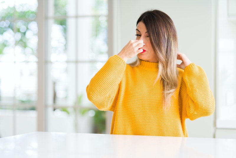 Young woman wearing winter sweater at home smelling something stinky and disgusting, intolerable smell, holding breath with fingers on nose