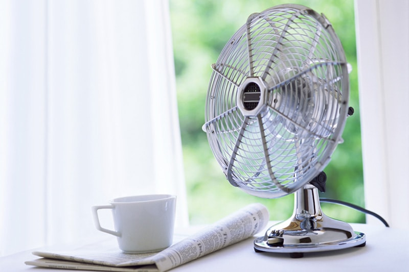 Fan on a side table next to a newspaper & cup of coffee, The Ever-Growing Importance of Indoor Air Quality & Energy Efficiency