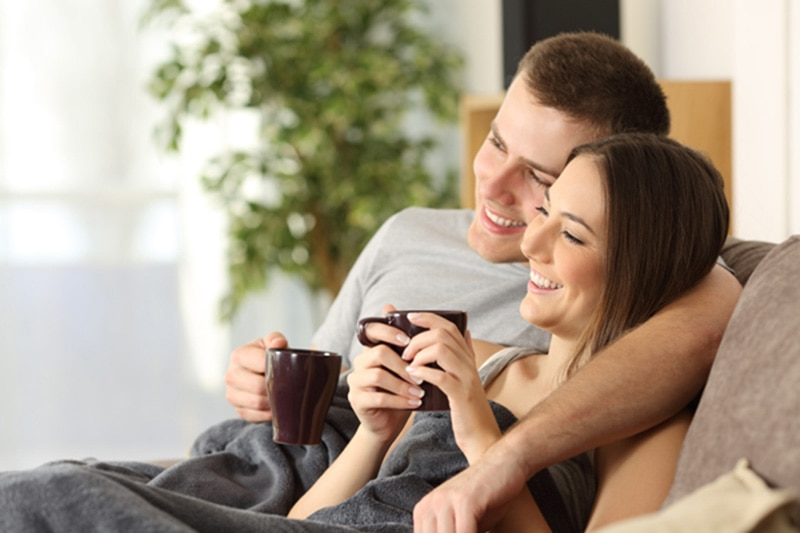 Couple enjoying a cup of coffee on a couch, How Can I Make My Furnace Last Longer? | Heating Service | Fishersville