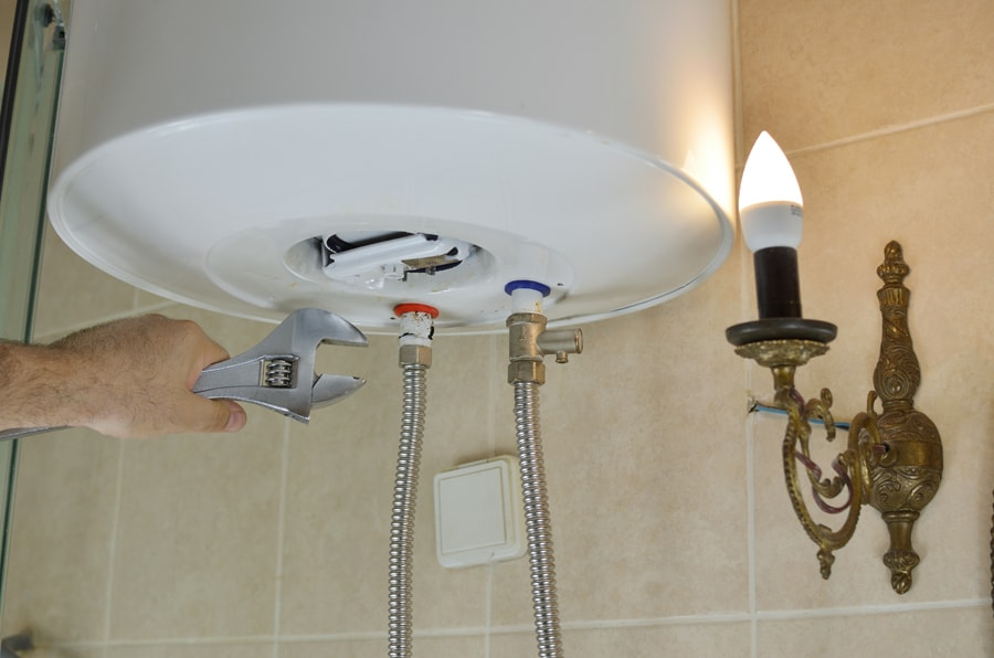 Repairing a boiler with a wrench in a bathroom,
