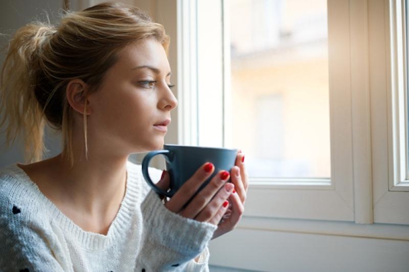 woman holding a coffee mug near a window